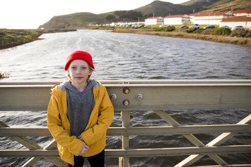 Portrait of boy standing on bridge over river against sky - CAVF52363