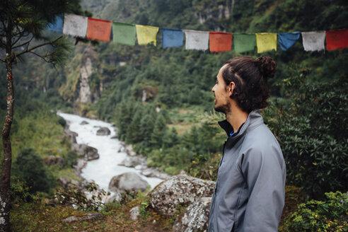 Hiker looking at river amidst mountains in Sagarmatha National Park - CAVF52387