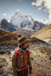 Hiker in warm clothing standing on mountain against sky at Sagarmatha National Park - CAVF52399