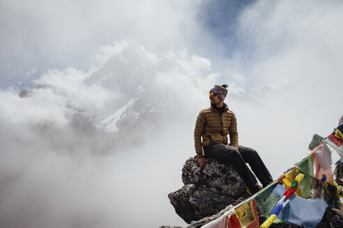 Hiker sitting on mountain against cloudy sky at Sagarmatha National Park - CAVF52408