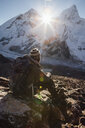 Hiker with backpack sitting on rock during sunny day at Sagarmatha National Park - CAVF52411