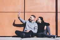 Boyfriend taking selfie with girlfriend while sitting by wall on sidewalk - CAVF52417