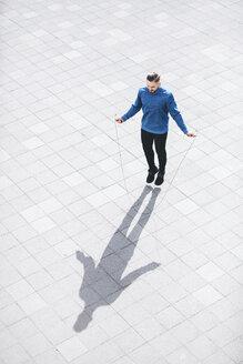 High angle view of man skipping on sidewalk in city - CAVF52423