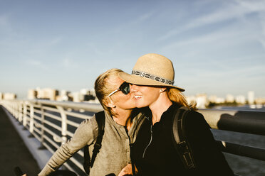 Loving mother kissing daughter on pier against sky in city - CAVF52444