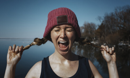 Woman with eyes closed screaming against sea during sunny day - CAVF52447