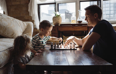 Side view of father playing chess with children on table at home - CAVF52453