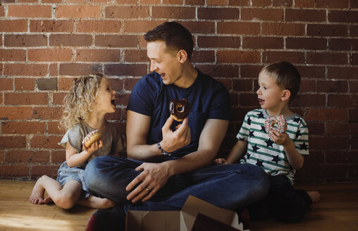 Happy father with children eating donuts while sitting on floor at home - CAVF52459