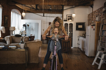 Happy mother with daughter riding bicycle at home - CAVF52462