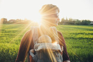 Mother wearing sunglasses while carrying son in baby stroller on grassy field against clear sky - CAVF52471