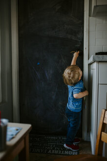 Side view of baby boy opening door at home - CAVF52597