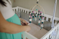 Midsection of pregnant woman holding hanging mobile over crib at home - CAVF52606