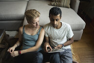 High angle view of multi-ethnic couple using digital tablet in living room at home - TGBF01154