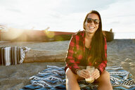 Woman on beach blanket drinking beverage from jar - TGBF01241