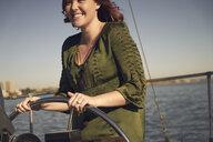 Happy woman steering sailboat on ocean - TGBF01292