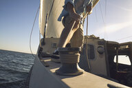 Low section of man pulling rigging on sailboat - TGBF01295