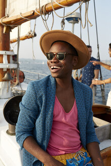 Smiling young man wearing hat while sitting on boat during summer - TGBF01448