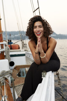 Portrait of attractive young woman sitting on edge of boat ion lake - TGBF01463