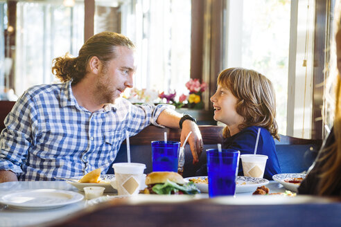 Side view of happy boy looking at father while sitting at restaurant - TGBF01541