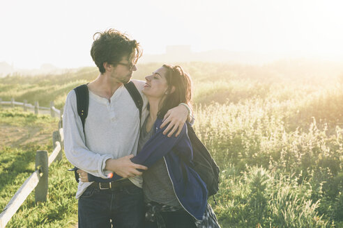Smiling woman embracing man while hiking on field during sunny day - TGBF01562