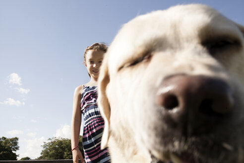 Portrait of happy girl with dog against blue sky - TGBF01568