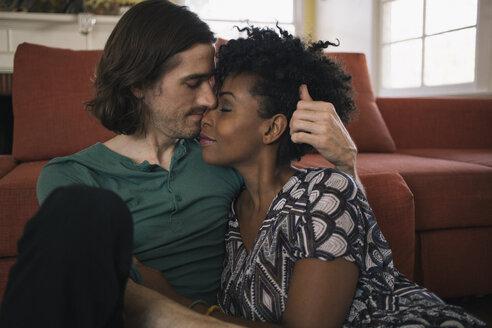 Romantic multiethnic couple sitting against sofa in living room - TGBF01580