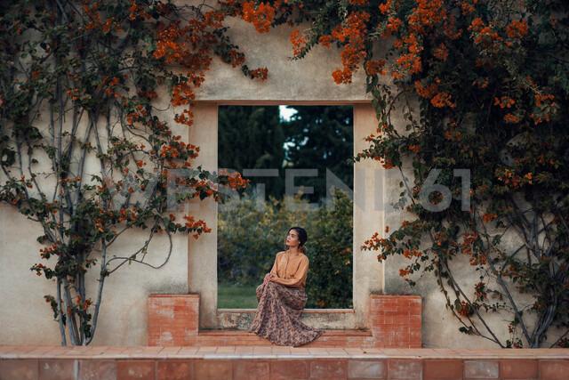 A woman sitting under a flower archway in autumn - INGF05477 - Ingram Image/Westend61