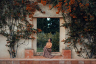 A woman sitting under a flower archway in autumn - INGF05477