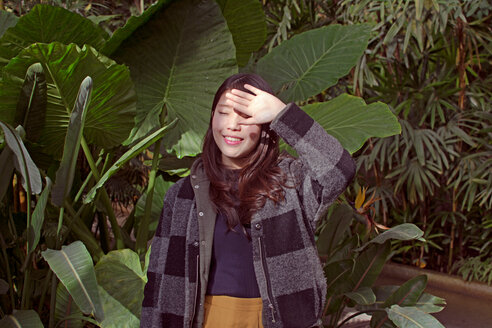 Portrait of a smiling young woman standing against plants - INGF05561