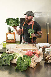 Vegan man choosing vegetables in his kitchen - REAF00348