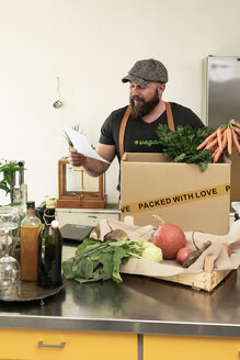 Mature man with delivery service packing organic vegetables in cardboard - REAF00369