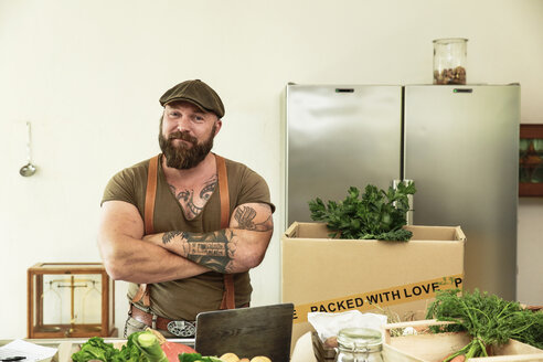 Owner of a delivery service for organic vegetables, standing proud in his kitchen - REAF00375