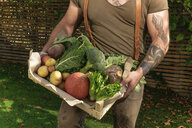 Mature man carrying crate with vegetables in his garden - REAF00387