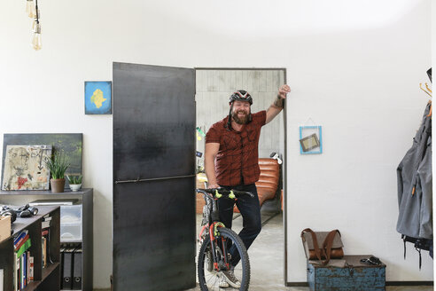 Portrait of laughing man with bicycle in office - REAF00405