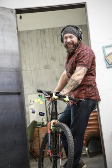 Portrait of happy man with bicycle wearing headphones in office - REAF00408