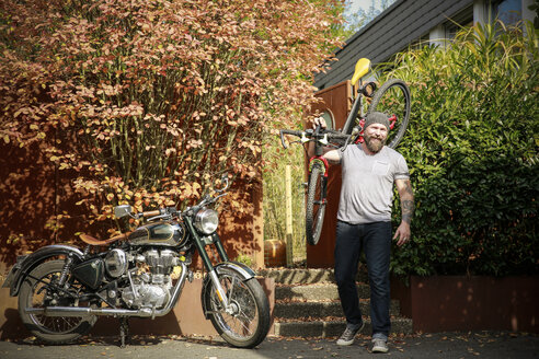Portrait of man switching from motorbike to bicycle - REAF00414