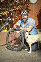 Portrait of smiling man with dog and bicycle - REAF00420