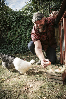 Man in his own garden, man holding egg of free range chickens - REAF00429