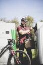 Portrait of man recycling glass bottle in bottle cyclist - REAF00442