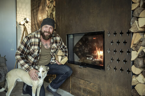 Portrait of smiling man with his dog in front of fireplace at home - REAF00454