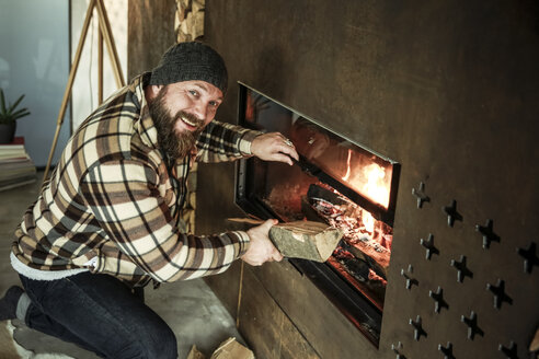 Portrait of bearded man kneeling in front of fireplace at home - REAF00457