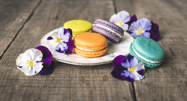 High angle view of colorful macaroons with flowers on wooden table - CAVF52633