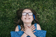 Overhead view of cheerful girl lying on grassy field at park - CAVF52663