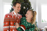 Cheerful couple standing against Christmas Tree at home - CAVF52672