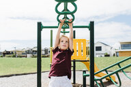 Boy hanging on monkey bars against cloudy sky at playground during sunny day - CAVF52681