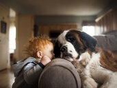 Baby boy playing with dog in living room at home - CAVF52693