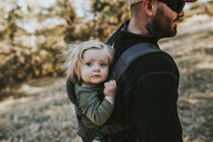 Father carrying cute daughter while hiking in forest - CAVF52699