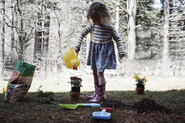 Girl watering potted plant in yard - CAVF52702