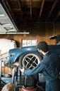 Side view of male mechanic repairing car in workshop - CAVF52714