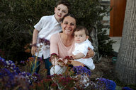 Portrait of happy mother with sons crouching against plants at park - CAVF52729