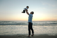 Happy father picking up son while standing at beach against sky during sunset - CAVF52735
